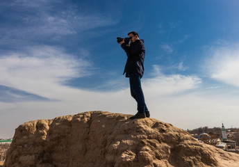 photographer in dark outfit and black sunglasses holding a camera steady in his hands and making a shot while standing on top of an ancient wall. Aerial view.