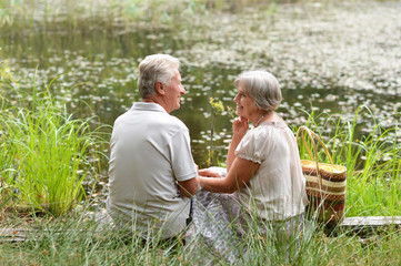 Portrait of nice mature couple sitting by pond