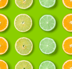 Citrus Fruits pattern on green background. Orange, Lime, Lemon slices background. Flat lay, top view. .  Pop art design, creative summer concept.