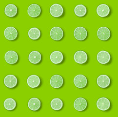 Fruit pattern of lime slices on green background. Flat lay, top view. .  Pop art design, creative...
