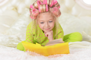 Lovely little girl with pink curlers reading