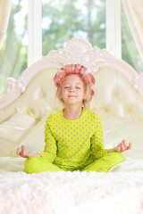 Lovely little girl with pink curlers meditating