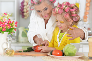 Portrait of senior woman and granddaughter at kitchen