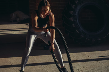 Young well trained muscular female athlete standing with jumping rope over brick wall gym background. Studio shot of female fitness model holding skipping rope in crossfit studio
