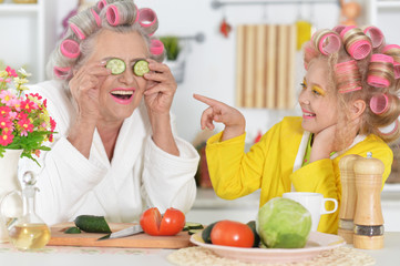 Senior woman and girl with pink hair curlers on head