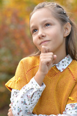 Cute little girl smiling in autumnal park