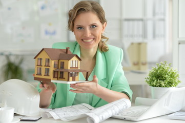 Young female architect holding small model of house in office
