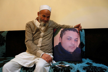 Father of late Musab Al-Hadi Al-Shibani Khamaj holds a picture of his son in Tripoli