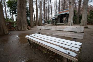 雪がうっすらと積もった公園のベンチ