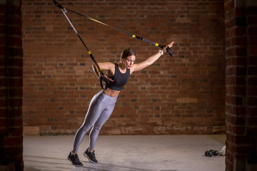 Fitness woman trainin on the TRX in the gym, doing exercise where stabilizing muscles are trained and the whole body is working, which makes such workouts truly functional.