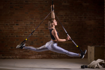 Young attractive female fitness coach does splits crossfit stretching with trx fitness straps in the gym or fitness studio