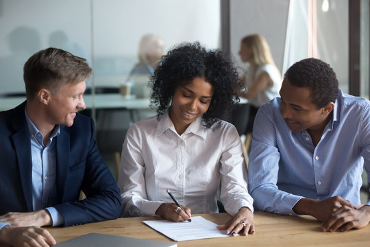 Black confident woman sitting with business partners signing contract
