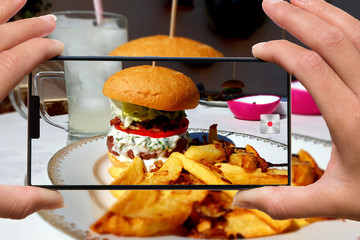 woman photographing on cell phone homemade hamburger and fries