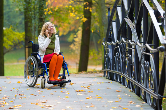 happy woman on wheelchair talking on the phone