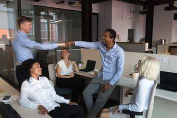 Diverse workers greeting each other with fist bumping