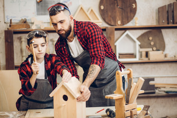 Time for family. Dad shows his little son how to make diy birdhouse in wooden workshop, using hand tools and wooden plank