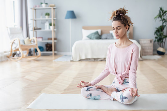 Portrait of attractive young woman working out at home, doing yoga exercise on white mat.