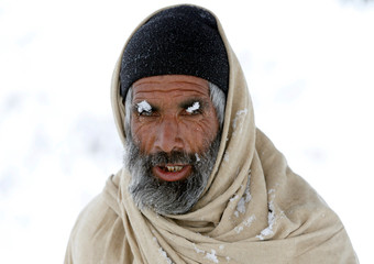 An Afghan man poses for a photo with snow-covered eyebrows on the outskirts of Kabul