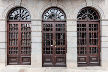 Three old wooden front doors with glass panes
