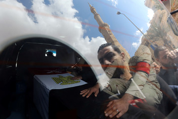 People are reflected in a vehicle window as a member of security forces sits next to a coffin containing the body of Egyptian military officer Abdulrahman Ali Mohammed during his funeral, in Cairo