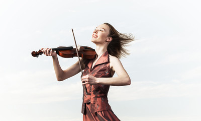 Woman violinist in red dress playing melody against cloudy sky