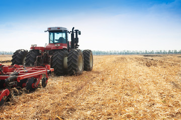 The tractor plows the field, cultivates the soil for sowing grain. The concept of agriculture.