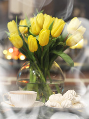 A bouquet of yellow tulips in a vase in the interior of a retro room. Retro interior with bouquet of tulips.