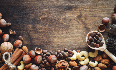 Different nuts on a wooden table. Cedar, cashew, hazelnut, walnuts and a spoon on the table. Many nuts are inshell and chistchenyh on a wooden background.