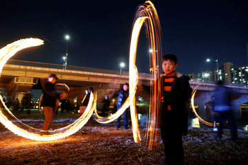 """Participants whirl cans filled with burning wood chips during a celebration ahead of """"Jeongwol Daeboreum"""", which is a traditional Korean holiday that celebrates the first full moon of the lunar calendar, at a park in Seoul"""