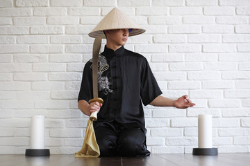 Asian young novice on a white brick wall