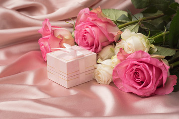 Gift box with silk ribbon and flowers on a gentle pink satin background. Festive concept.