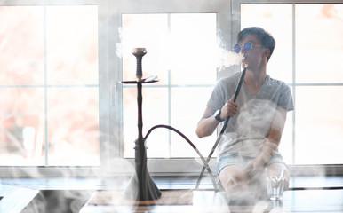 Man in sunglasses smoking a hookah