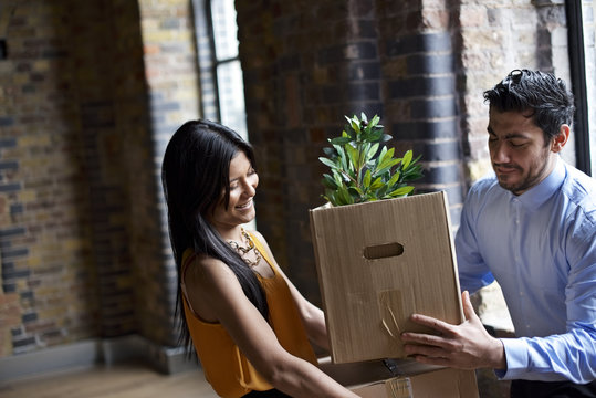 Female and male colleagues moving in to new office
