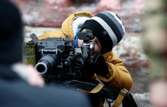 """Boy aims a machine gun during the event """"Winter fun"""" at the Belarusian Interior Ministry's special forces unit base in Minsk"""