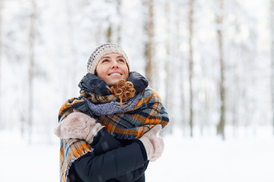 Waist up portrait of happy young woman in winter forest having fun and enjoying snow, copy space