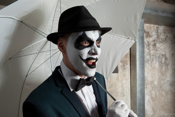 Evil clown holding white umbrella