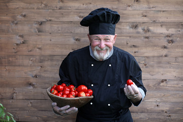 Chef old in uniform with fresh vegetables