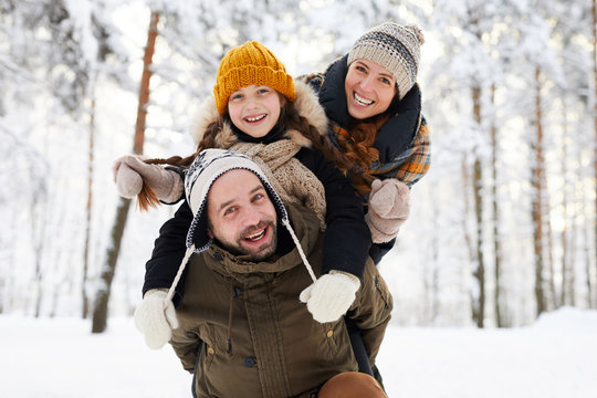 Portrait of playful happy family in winter forest looking at camera and smiling, copy space