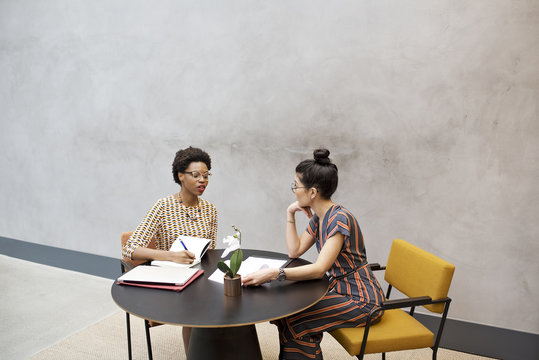 Black African and Asian businesswomen in a meeting