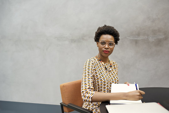 Portrait of a black African businesswoman writing at a desk