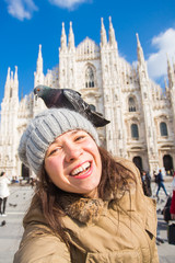 Travel, holidays and winter vacations concept - Happy young woman take selfie photo with funny pigeons in front of Duomo Milan Cathedral