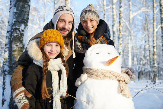Waist up portrait of happy family building snowman in winter forest and smiling at camera, copy space