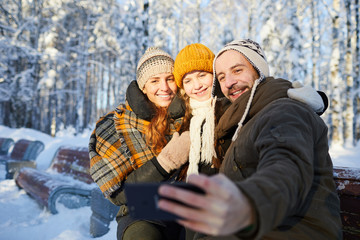 Portrait of happy family taking selfie photo in beautiful winter forest, copy space