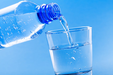 Pouring drinking water from bottle into glass on blue background.