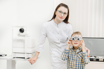 Pediatric Doctor ophthalmologist checks vision of child boy. Concept selection of glasses lenses.