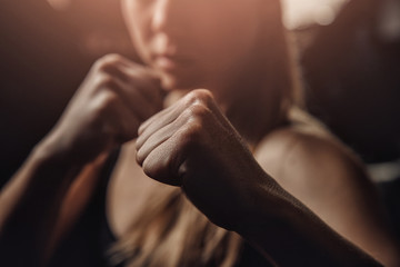 Young female boxer preparing to punch bag. concept of will win, power of spirit