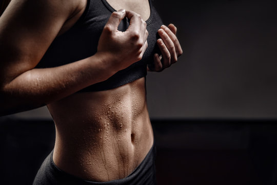 Closeup of drop of sweat on skin abdomen woman after workout. Dark background. Copy space