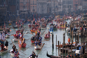 Venetians row during the masquerade parade on the Grand Canal during the Carnival in Venice