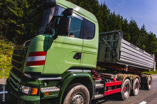Heavy green car carrier truck transports on highway road on
