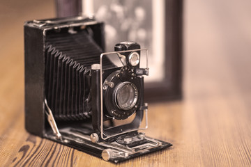 Close up image of old vintage dusty camera with old image on blurred background, selective focus. Wooden table, indoors, retro effect, copy space.